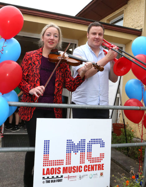 Rosa Flannery and jay Ritchie standing holding instruments outside the Laois Music Centre.