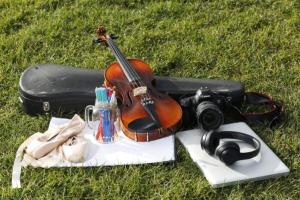 PLATFORM 31 promotional image of a violin, headphones, paper, coloured pens and dance shoes